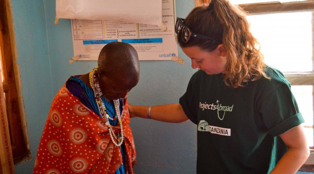 On the Public Health Internship for teenagers in Tanzania, a student helps take the vital signs of a Maasai woman during an outreach.